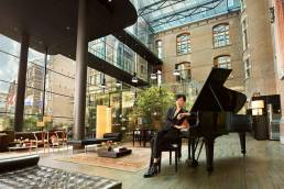 The Set Hotels Revenue Growth (image of girl at piano in Conservatorium Hotel)
